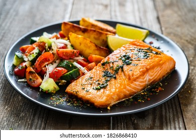 Fried salmon fillet with fried potatoes, lime and vegetable salad served on black plate on wooden table