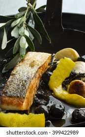 Fried salmon with olives, garlic and lemon peel in a iron pan