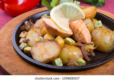Fried salmon with potatoes served on a hot sizzler
