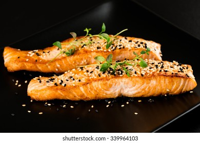 Fried salmon with sesame seeds and herbs on black plate close up