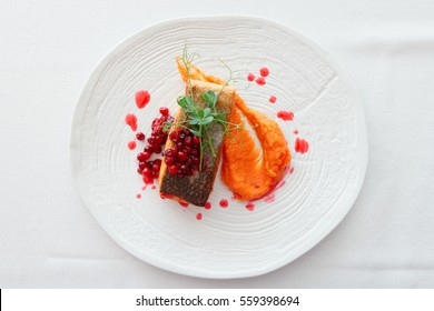Fried salmon steak with pumpkin puree, red berry sauce and herbs on white plate