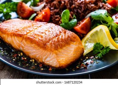 Frittiertes Lachssteak mit rotem Reis und Gemüse auf Holztisch