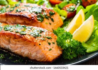Frittierte Lachssteaks mit Gemüse auf Holztisch