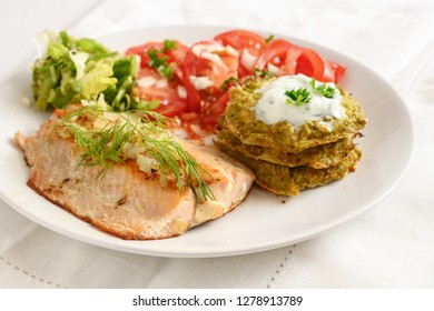 fried salmon with vegetable pancakes and tomato salad, healthy low carb diet food, white plate on white tablecloth, selected focus, narrow depth of field