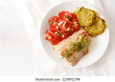 fried salmon with vegetable pancakes and tomatoes, low carb diet food on white table with copy space, high angle view from above