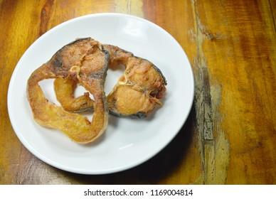fried salty striped catfish slice on white dish