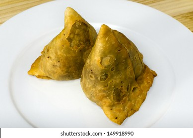 Fried samoosa on a white plate.