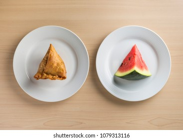 Fried samosa and piece of fresh watermelon placed side by side on white plates. A concept. A healthy Iftar food habits during holy month of Ramadan. Part 1 of series of 3 photos.