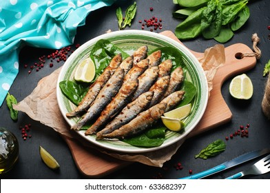 Fried sardines (sea fish) on spinach leaves lie on a green plate on a dark background. Useful and tasty dietary (vegetarian) home-cooked dish.