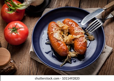 Fried sausage with onions in a plate.