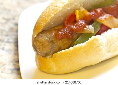 Fried sausage onions and red, green, and yellow bell peppers on sandwich bun and tomato sauce