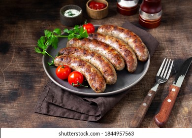 Fried sausages. Grilled sausages with spices, sauce, tomatoes and parsley. Delicious meat sausages in a ceramic plate