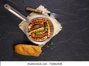 Fried sausages with parsley in a pan on black background