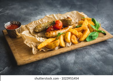 Fried sausages with potatoes and pickled tomato on a wooden plate. Closeup view.
