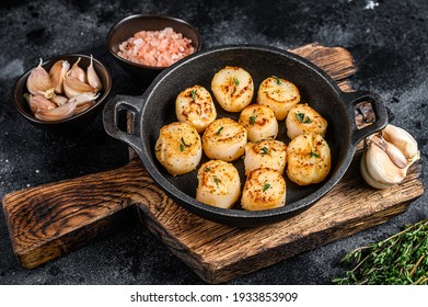 Fried scallops with butter sauce in a pan. Black background. Top view.