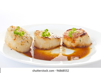 fried scallops with soy sauce on white plate
