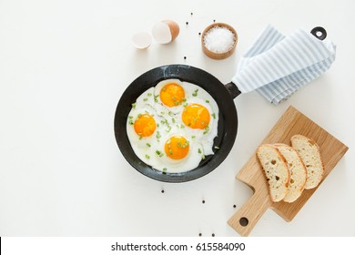 Fried scrambled eggs in a frying pan, bread and salt on a white background