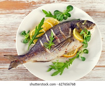 Fried sea bream on plate with  a lemon.  Healthy food.