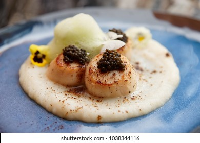 Fried sea scallops with caviar, celery puree and molecular froth on blue clay plate