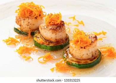Fried sea scallops with orange zest in plate