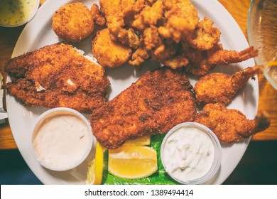 Fried seafood platter top view of local dish from Key West, Florida, Conch fritters, cod fish in oily batter fry.