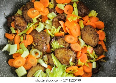 Fried seitan in a pan with carrots and celery sticks.