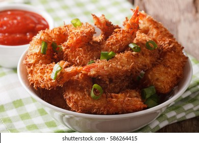 Fried shrimp in coconut breaded close up in a bowl and the sauce on the table. horizontal