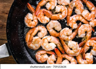 Fried shrimp with garlic on pan, preparing dish with seafood, mediterranean cuisine concept