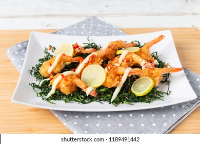 Fried Shrimp with Lime Cream Sauce and deep fried kale on wooden table