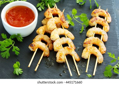 Fried shrimp on skewers with salad from carrots.