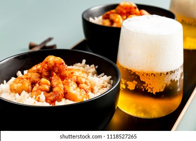 Fried shrimp and rice in a black bowl. Glass with beer. The background is gray.