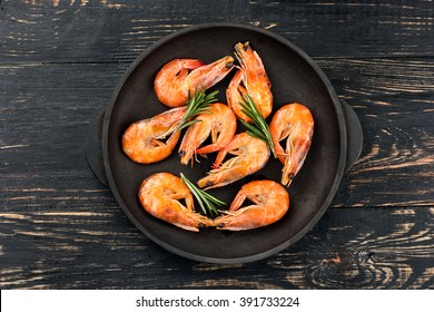 Fried shrimp with rosemary in a portioned frying pan on a dark table top view