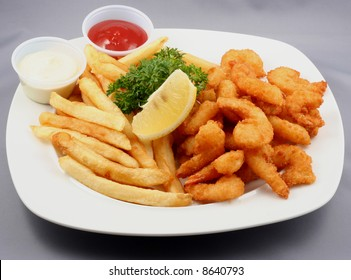 fried shrimps with fries and ketchup and sauce