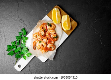 Fried shrimps with lemon on a cutting board and and black background, top view, free space for text