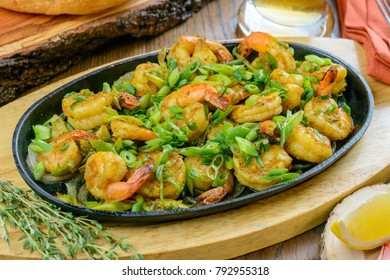 Fried shrimps on oval fry pan garnished with herbs and greens