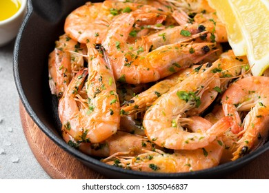 Fried shrimps in shell with parsley, coriander, garlic and oil in pan. Tasty mediterranean cuisine, vegetarian food, healthy protein