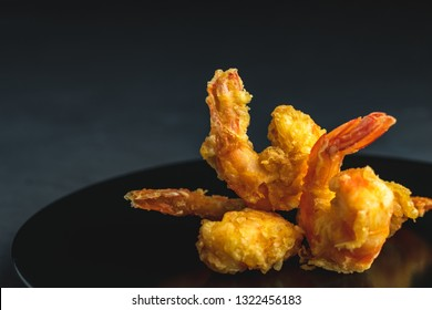 Fried Shrimps tempura in black plate on dark concrete surface background. Copy space for you text. Seafood tempura dish served japanese or eastern Asia style
