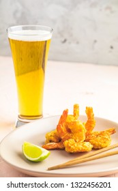 Fried Shrimps tempura with lime in light plate and glass of beer on pink or peach concrete surface background. Copy space Seafood tempura dish served japanese or eastern Asia style with chopsticks