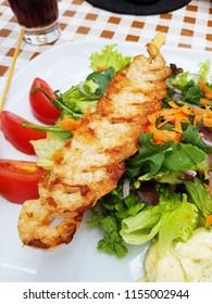 Fried skewers shrimp. Delicious prawn salad.