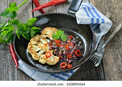 Fried  slice of cauliflower topped with red parsley onions with red chili peppers