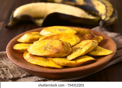 Fried slices of ripe plantains, traditional and popular snack and accompaniment in Central and Northern South America, photographed with natural light (Selective Focus on the front of the top slice)