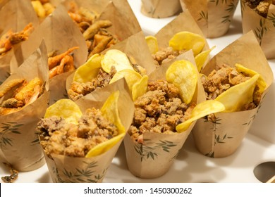 Fried snacks in paper cups on the city market, fast street food