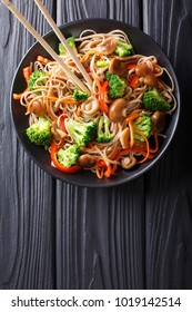 fried soba noodles with mushrooms, broccoli, carrots, peppers closeup on a plate on a table. Vertical top view from above