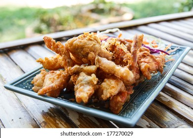 Fried soft shell crab with garlic, salad and carrot in a blue plate on a wooden table in restaurant.