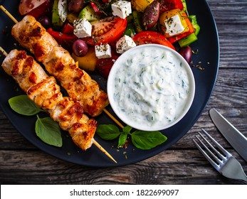 Frittierte Souvlaki, griechischer Salat und Tzatziki auf Holztisch