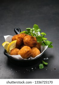 Fried Spanish bacalao croquettes in iron pan made with breaded salted codfish and served as traditional tapas or snacks. Dark background with Copy space. Mediterranean food.