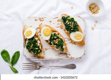 Fried spinach, egg and pine nuts sandwiches or bruschetta on light background. Delicious healthy breakfast or snack. Top view.