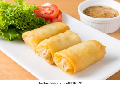 fried spring rolls on white plate with sauce