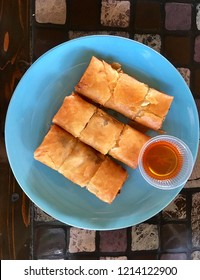 Fried spring rolls serves with sweet sauce on blue dish