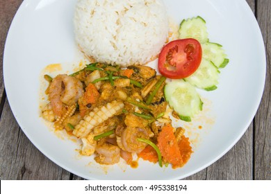 fried squid with curry , shrimp with chili eat with rice ,carrot , cucumber and tomato.Thai food. Asian food.select focus.